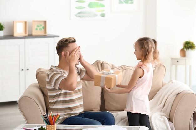 Милая маленькая девочка встречает своего папу с днем отца дома
