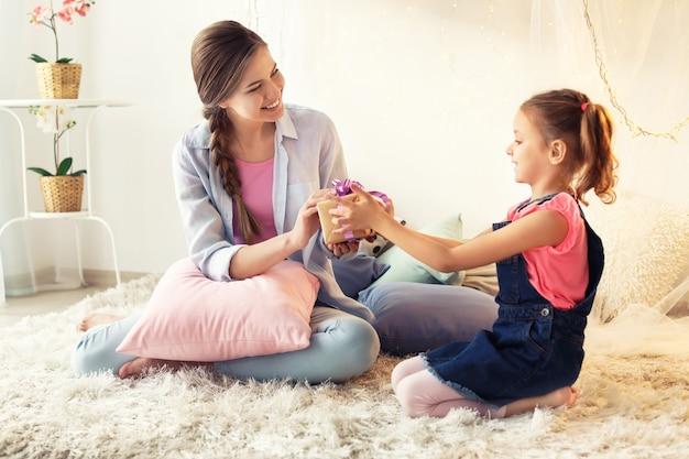 Милая маленькая девочка приветствует свою мать дома