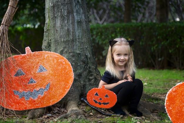 Cute little girl in halloween costume sitting near pumpkin decoration