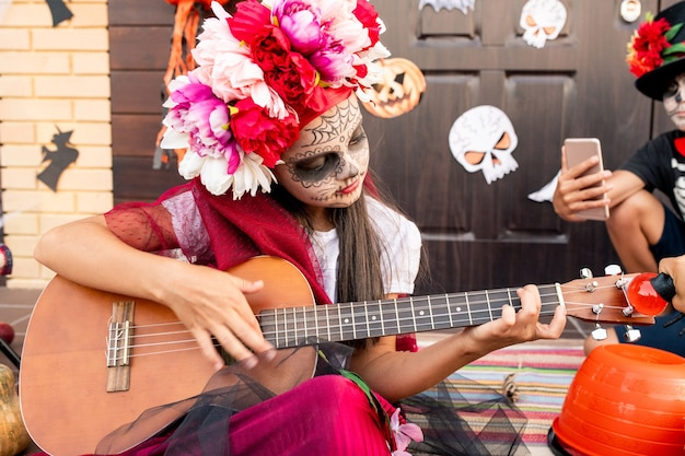 Cute little girl in halloween costume sitting on staircase and playing guitar while serious boy by the door taking photo of her on smartphone