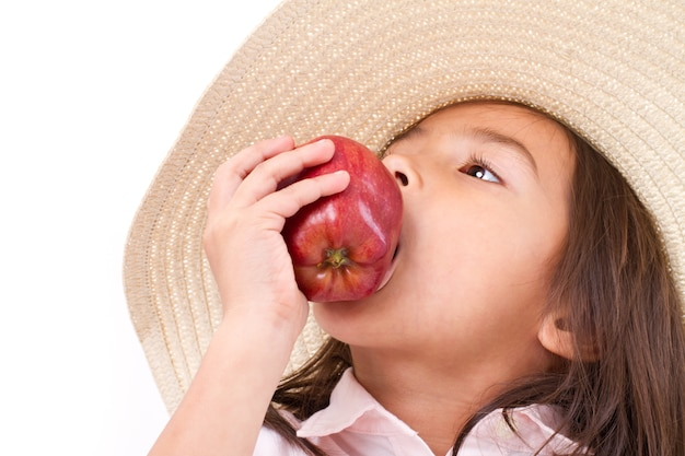 Cute little girl, hand holding, biting red apple