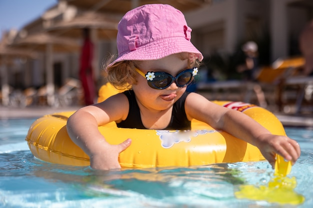 Cute little girl in a hat and sunglasses plays in the pool while sitting in a swimming circle.