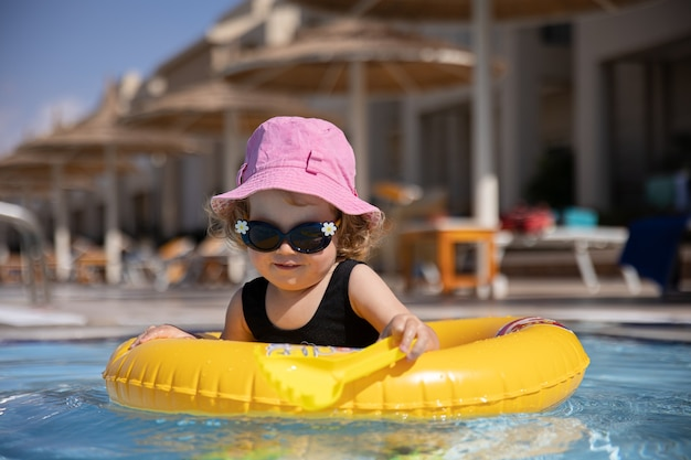 Cute little girl in a hat and sunglasses plays in the pool while sitting in a swimming circle
