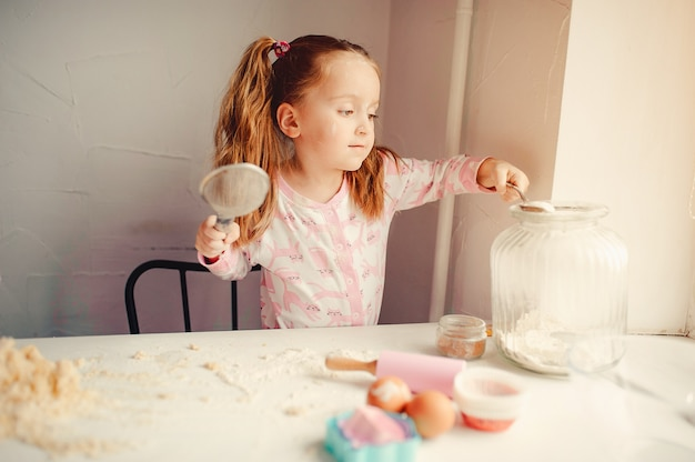 Cute little girl have fun in a kitchen