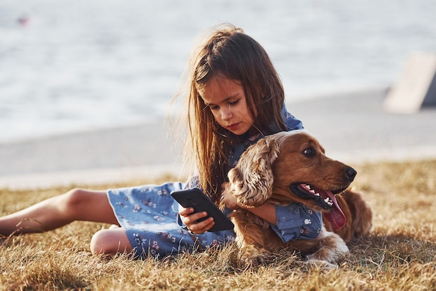 Cute little girl have a walk with her dog outdoors at sunny day