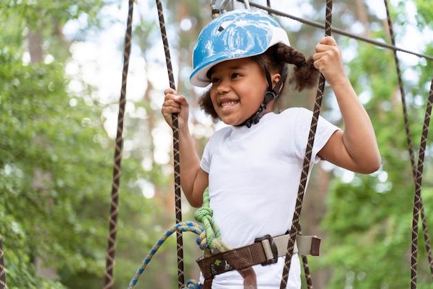 Bambina carina che si diverte in un parco avventura