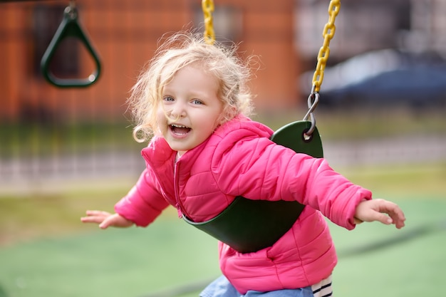 Cute little girl having fun on outdoor playground