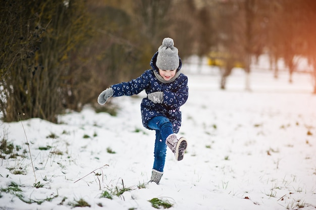 冬の日に屋外で楽しんでいるかわいい女の子。