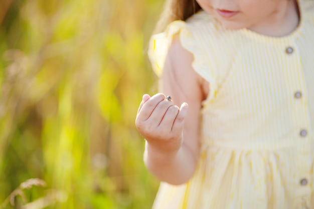 Cute little girl having ladybug on her hand. close-up view of little girl wearing headband playing with ladybug in nature. close up photo. copy space