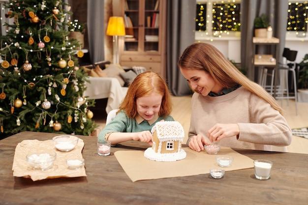 그녀의 어머니를 돕는 귀여운 소녀 장식 맛있는 진저 브레드 하우스의 지붕을 뿌린다