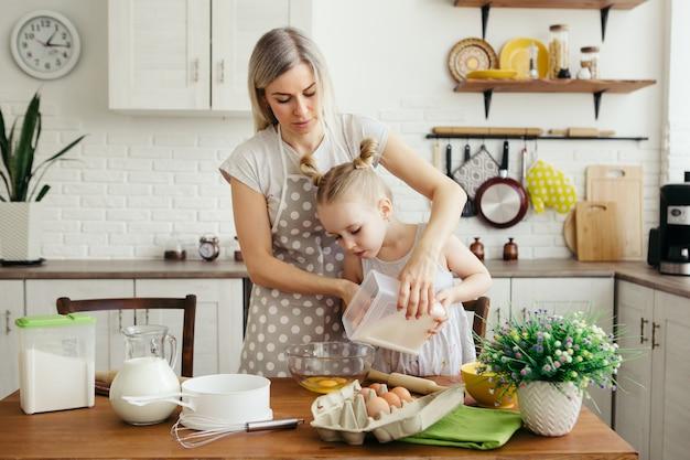 かわいい女の子は、お母さんがキッチンでクッキーを焼くのを手伝います。幸せな家族。調色。