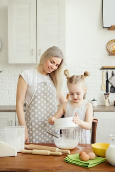 Cute little girl helps mom bake cookies in the kitchen. happy family. toning.