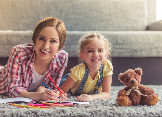 Cute little girl and her beautiful mother are drawing.