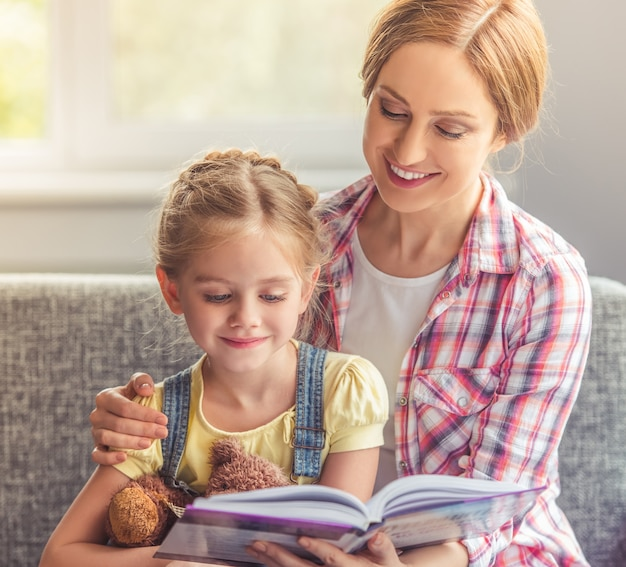 Cute little girl and her beautiful mother are reading book.