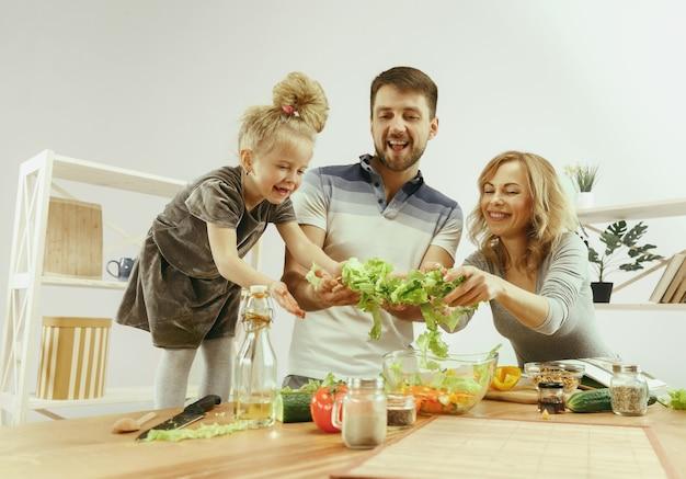 La bambina sveglia ed i suoi bei genitori stanno tagliando le verdure in cucina a casa
