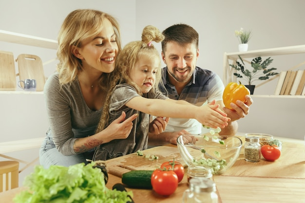 Cute little girl and her beautiful parents are cutting vegetables and smiling while making salad in kitchen at home. family lifestyle concept