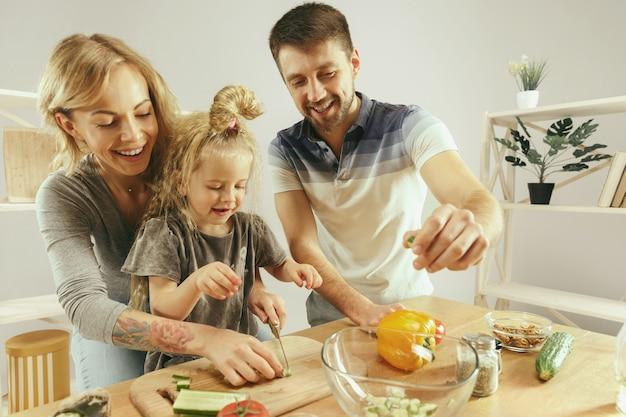 La bambina sveglia ed i suoi bei genitori stanno tagliando le verdure