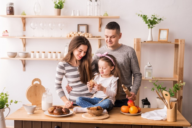Cute little girl and her beautiful parents prepare food and smile while cooking in the kitchen at home. knead the dough on pancakes and rolls