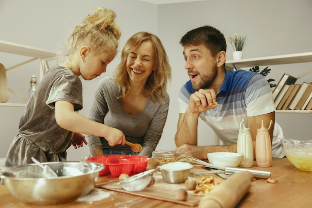 Cute little girl and her beautiful parents preparing the dough for the cake in kitchen at home. family lifestyle concept