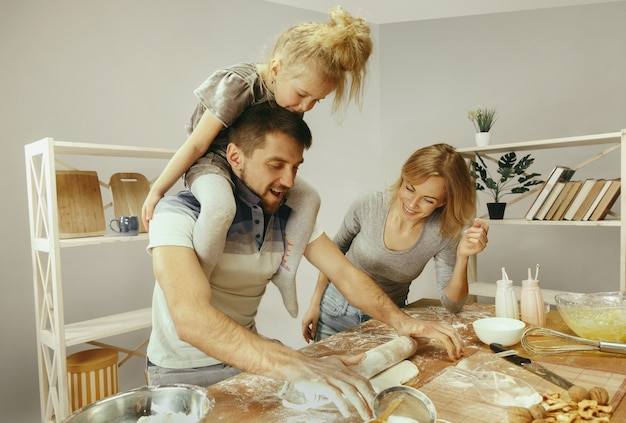 Bambina sveglia ed i suoi bei genitori che preparano la pasta per la torta in cucina a casa. concetto di stile di vita familiare