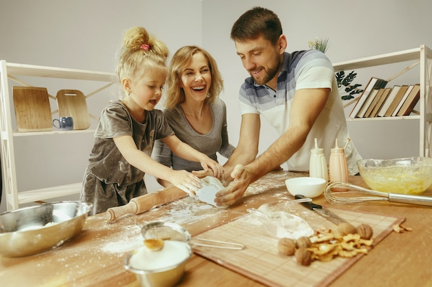 Cute little girl and her beautiful parents preparing the dough for the cake in kitchen at home