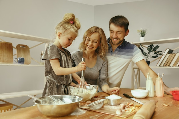 Cute little girl and her beautiful parents preparing the dough for the cake in kitchen at home.