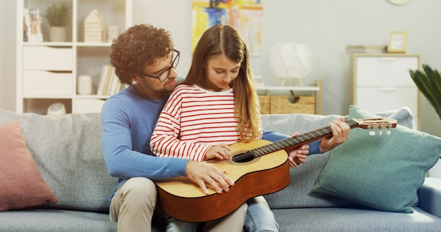 Cute little girl and her father are playing guitar and smiling while sitting on on sofa .