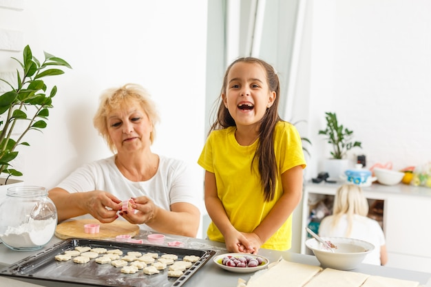 Cute little girl and her grandmother make cookies on kitchen.