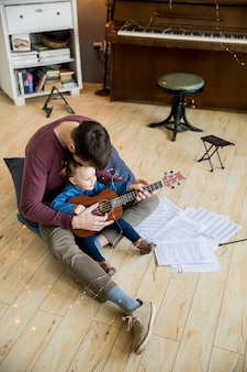 Cute little girl and her handsome father are playing guitar and smiling while sitting  in the room