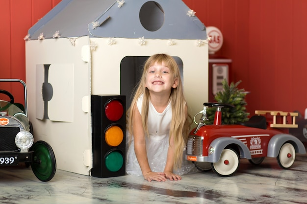 Cute little girl hiding in a cardboard house and playing with a big toy fire engine.