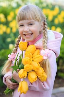 美しい花の背景に黄色いチューリップの花束を持っているかわいい女の子。ピンクのコートを着た女の子。