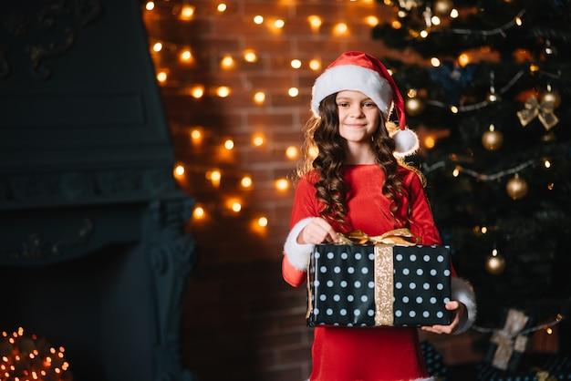 赤いサンタの衣装でクリスマスツリーの近くに贈り物を持っているかわいい女の子
