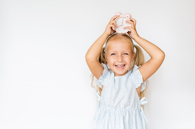 Cute little girl holding alarm clock on white  with copyspace