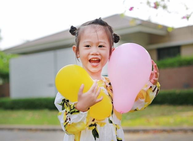 Cute little girl holding balloons in the park, smiling and having fun.