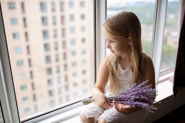 Cute little girl holding bouquet of purple flowers