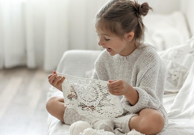 Cute little girl holding a handmade openwork napkin in her hands.