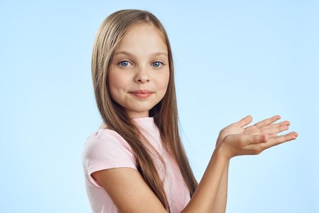 彼女の先を見越して彼女の手を繋いでいるかわいい女の子トリミングビューの青い背景