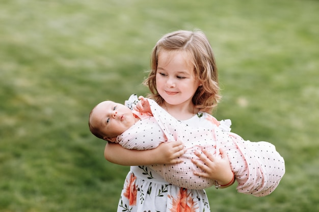 야외에서 그녀의 어린 신생아 동생을 들고 귀여운 소녀