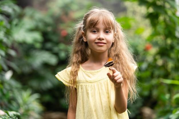 Милая маленькая девочка держит живую красивую бабочку на руке