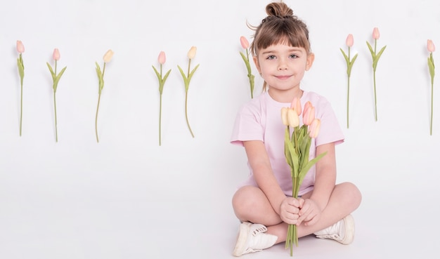Cute little girl holding tulips