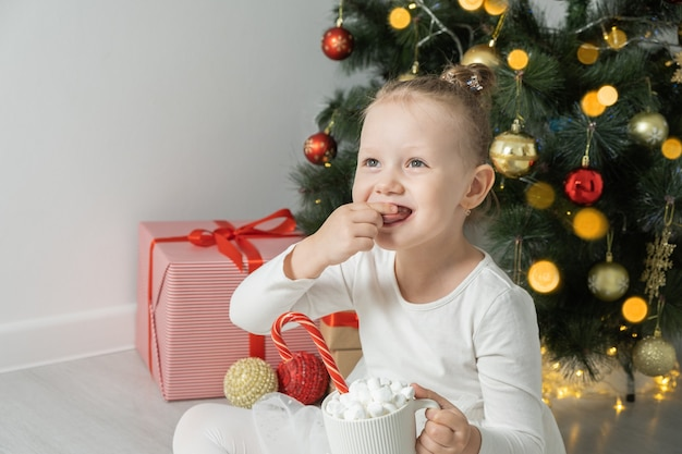 Cute little girl holds a cup of hot chocolate or cocoa eats a marshmallow near christmas tree.