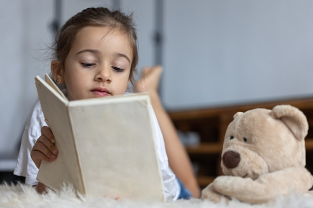 Carina bambina a casa, sdraiata sul pavimento con il suo giocattolo preferito e legge un libro.