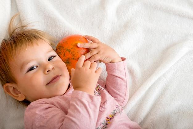 Cute little girl hugging a pumpkin on a bed indoors. copyspace