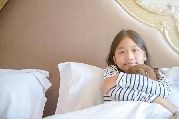 Милая маленькая девочка обнимает плюшевого мишку, сидя на кровати, концепции счастья и любви