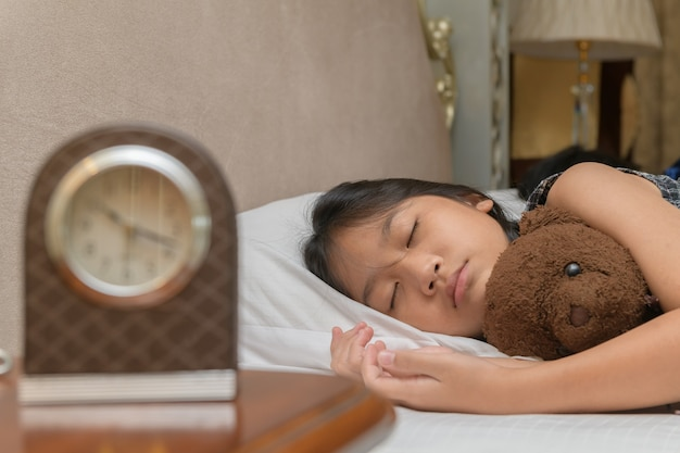 Милая маленькая девочка обнимает спящего плюшевого мишку, лежа в постели, счастливый маленький ребенок, обнимая игрушку, засыпает на мягкой подушке