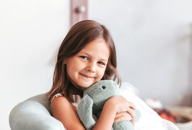 かわいい女の子が軽い子供の寝室でぬいぐるみを抱きしめます