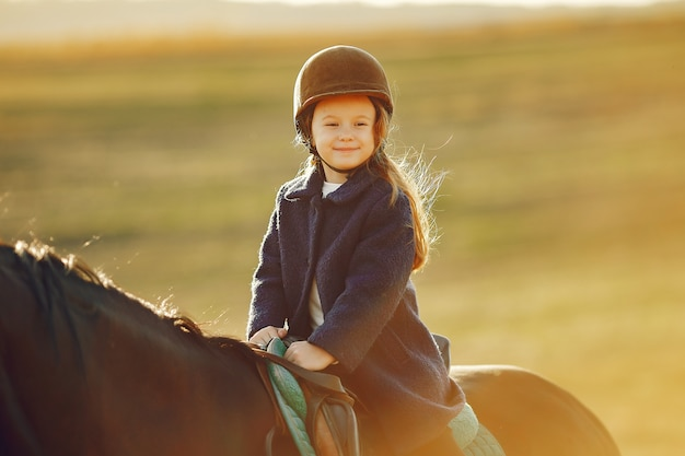馬と秋のフィールドでかわいい女の子