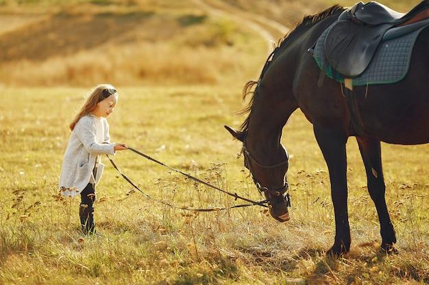 Милая маленькая девочка в осеннем поле с лошадью