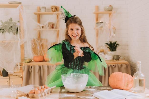Милая маленькая девочка в зеленом костюме ведьмы или феи на хэллоуин готовит тыквенный пирог