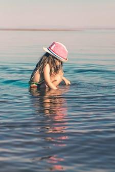 니트 수영복과 분홍색 모자를 쓴 귀여운 소녀가 바다에 앉아 물장난을 하고 있다